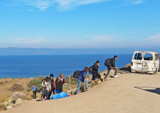 Exilés marchant avec leurs bagages en face de la mer.