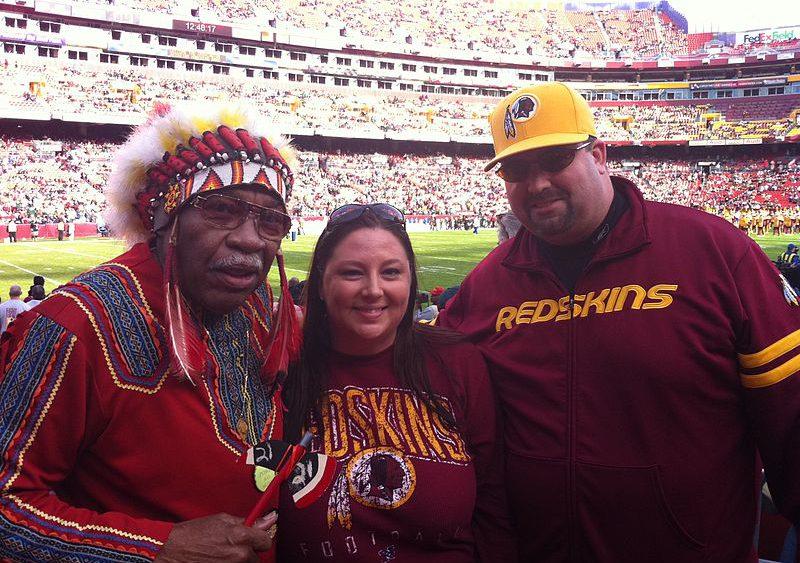 Trois personnes lors d'un match des Redskins arborant des accessoires dont certains avec des symboles traditionnels amérindiens